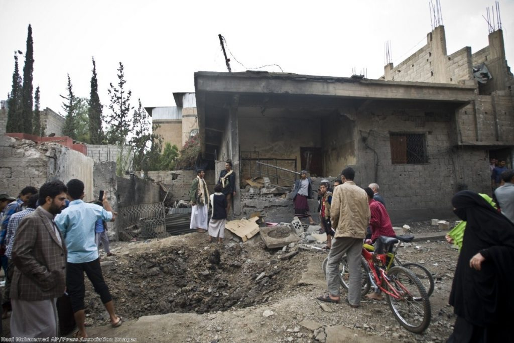 People stand by a crater and a house damaged by a Saudi-led airstrike in Sanaa, Yemen, Wednesday, May 27, 2015