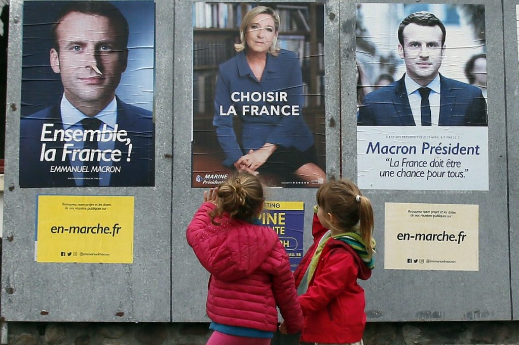 Children walk past election campaign posters for French centrist presidential candidate Emmanuel Macron and far-right candidate Marine Le Pen, in Osses, southwestern France.