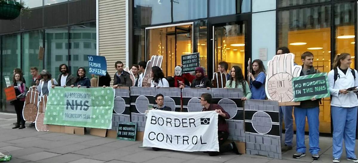 """""""Healthcare professionals and activists set up an 'immigration checkpoint' outside the government building to highlight the policy"""""""