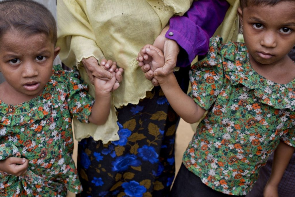 A Rohingya Muslim woman holds the hands of her grandchildren at Balukhali refugee camp in Ukhiya, Bangladesh