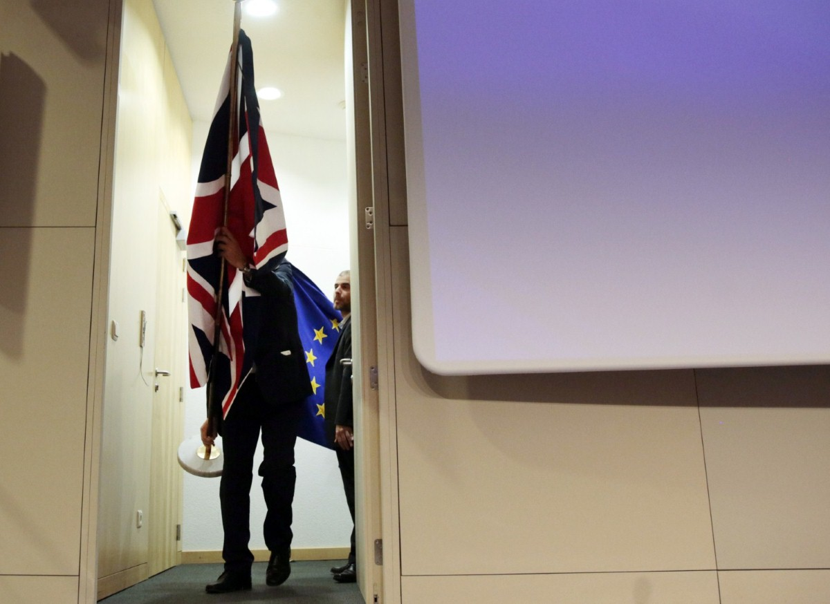 Members of protocol prepare to put up British and EU flags prior to a conference between Michel Barnier and David Davis last month