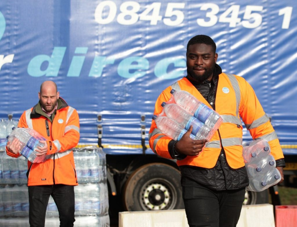 Thames Water workers help distribute bottled water in Hampstead, north London, after thousands of people were left without water.