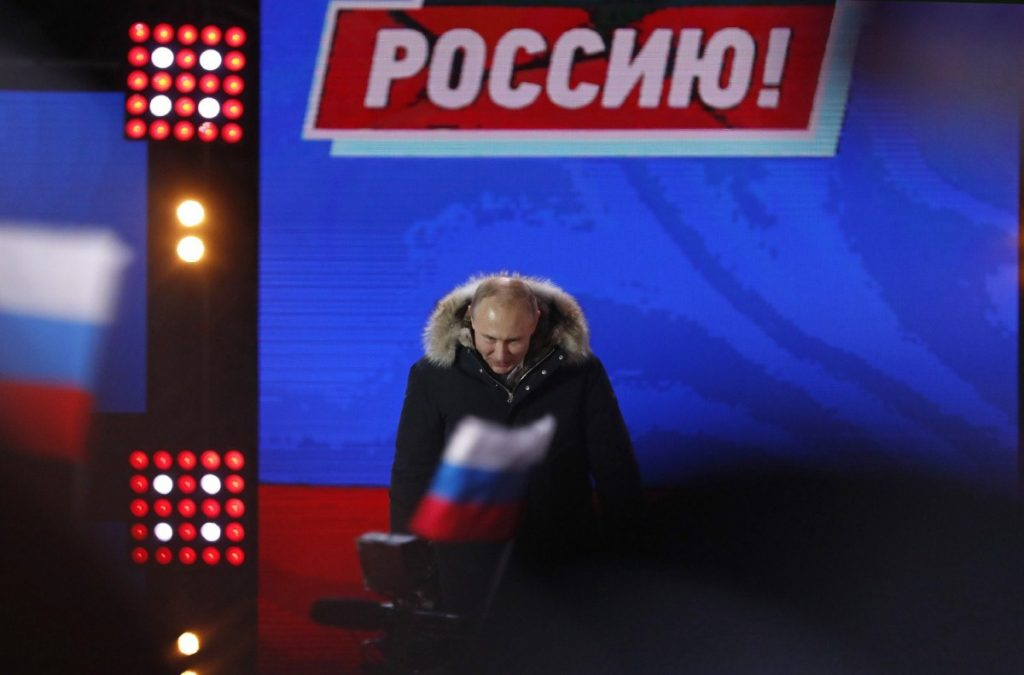 Putin addresses supporters during a rally near the Kremlin yesterday, as he coasts to another election victory