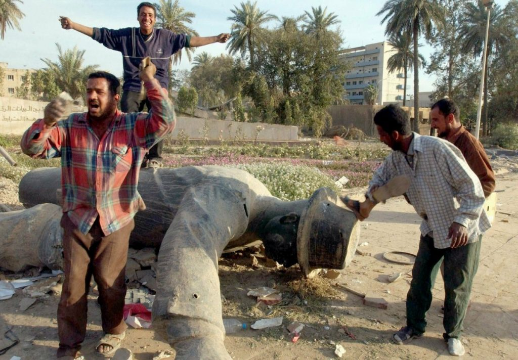 Iraqis celebrate around a toppled statue of Saddam Hussein on April 12th 2003.