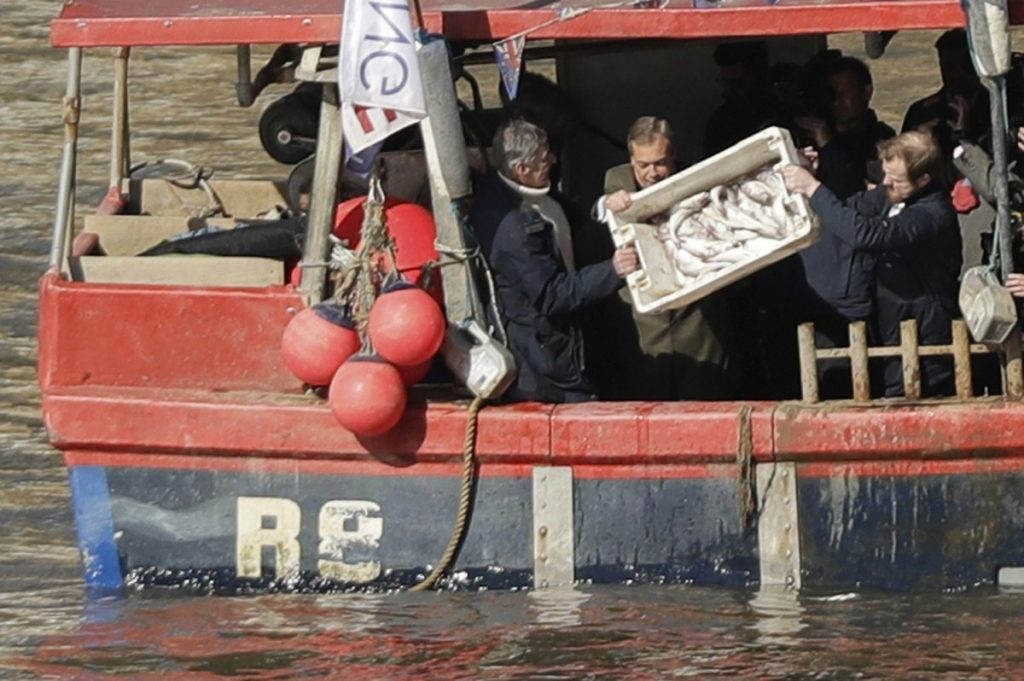 Nigel Farage helps tip a container of fish into the Thames on Wednesday in a protest stunt over the transition deal
