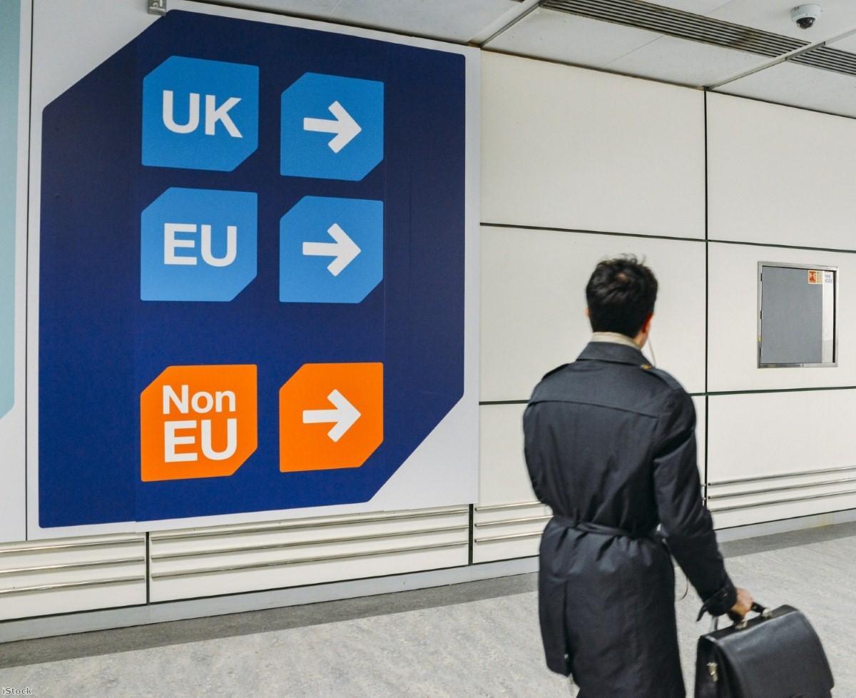 Passenger walks past UK, EU and non-EU sign at the airport   Copyright: iStock