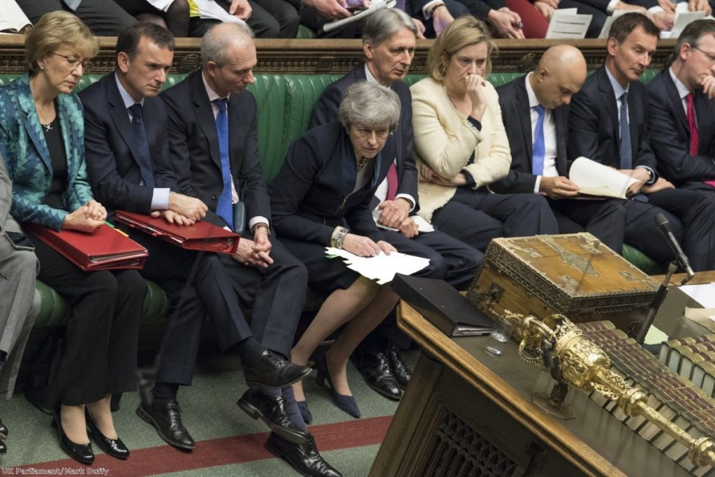 Theresa May leans forward during PMQs. She is reluctantly allowing domestic preparation to start for European elections.