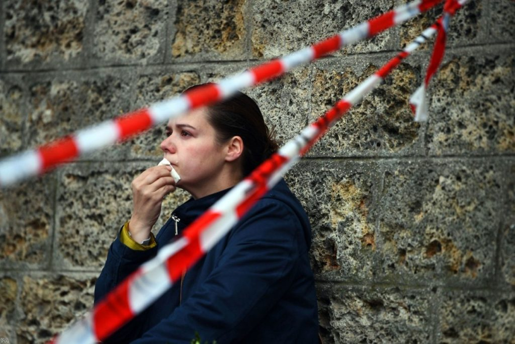 An onlooker in Paris wipes away a tear at a police cordon line near the Notre Dame Cathedral yesterday.