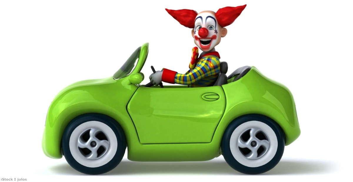 A clown-car, tottering down a high speed motorway, surrounded by heavy-duty vehicles travelling at speed.