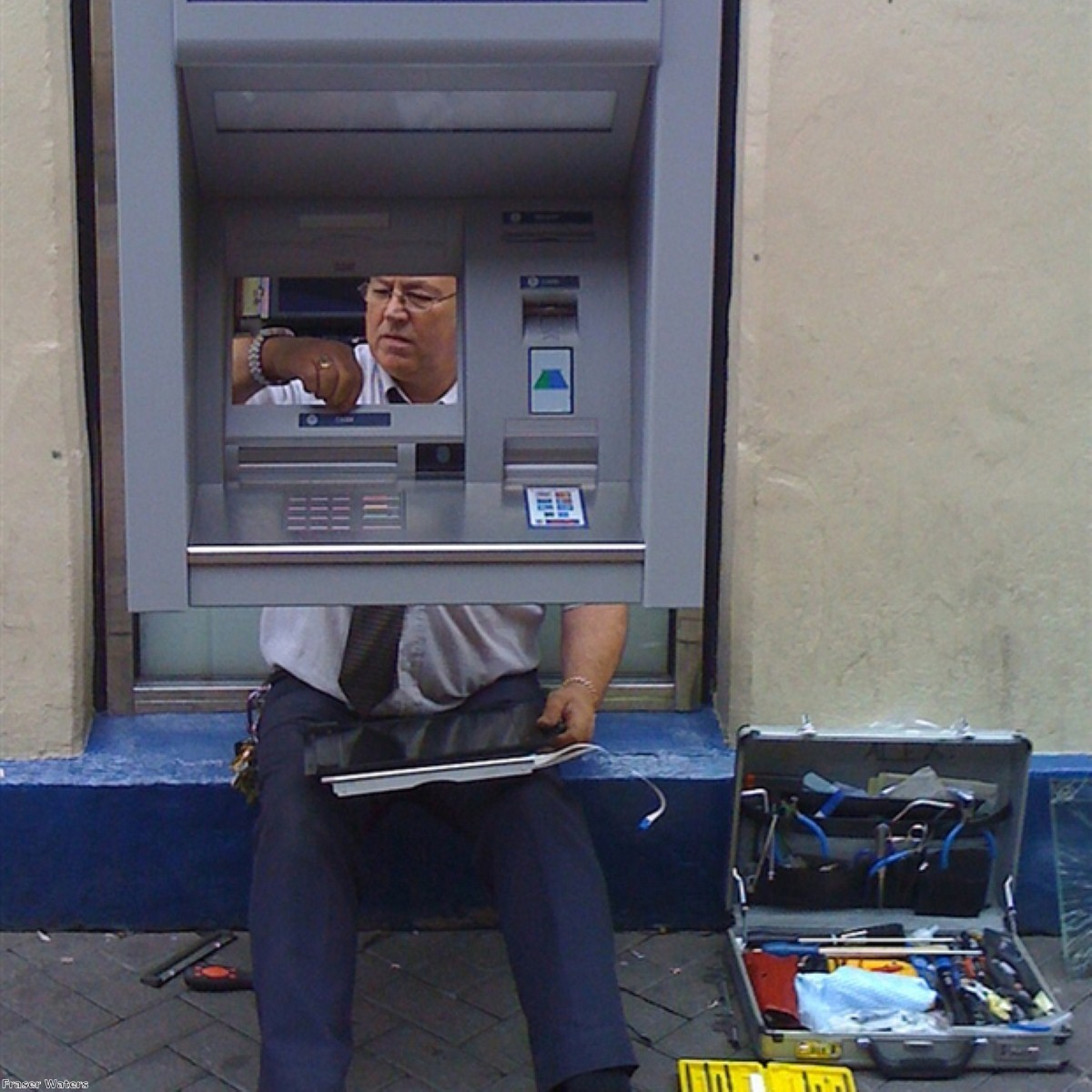 A man fixes a cash machine on a British street. Government sources admit the minimum wage could be cut, but analysts warn of effects on demand.