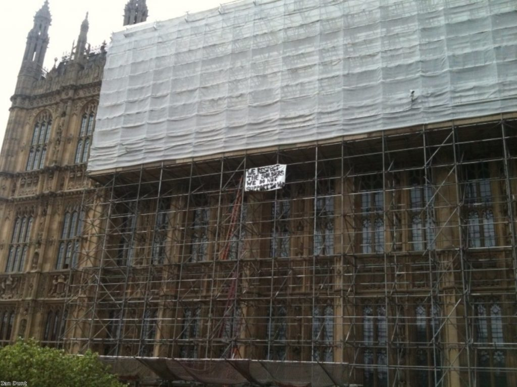 Peace protesters unfurl their banner on top of parliament today