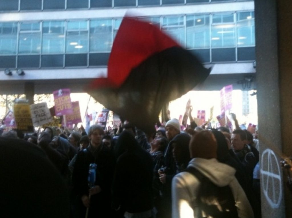 An anarcho-communist flag flies as activists destroy Tory HQ during a tuition fees protest