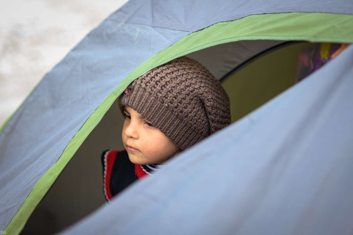 A young girl from Syria, who is on the run with her family, looks out of a tent in the Turkish border town of Edirne, near the Pazarkule-Kastanies border crossing, last spring.