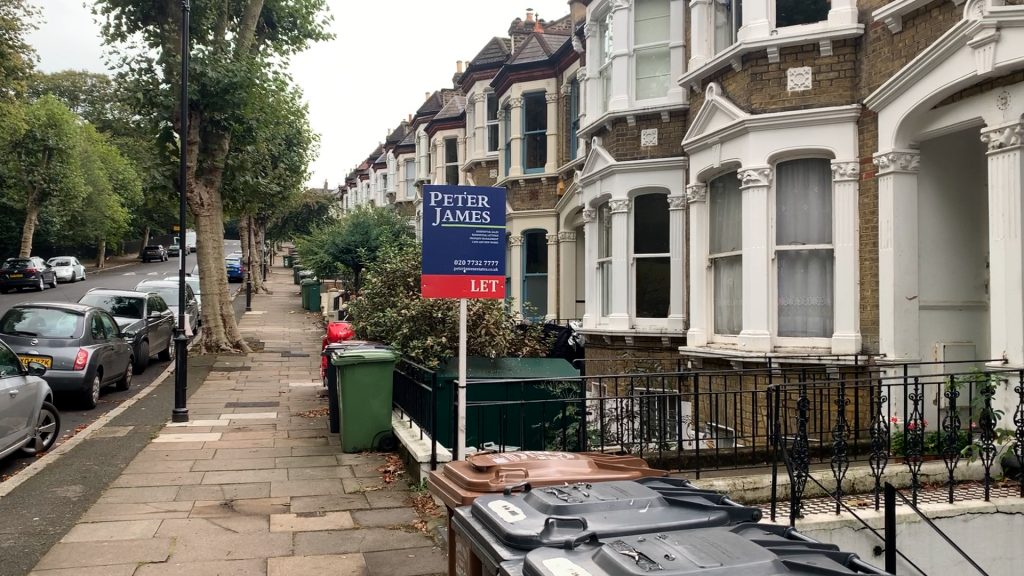 A to-let sign in front of some terraced houses