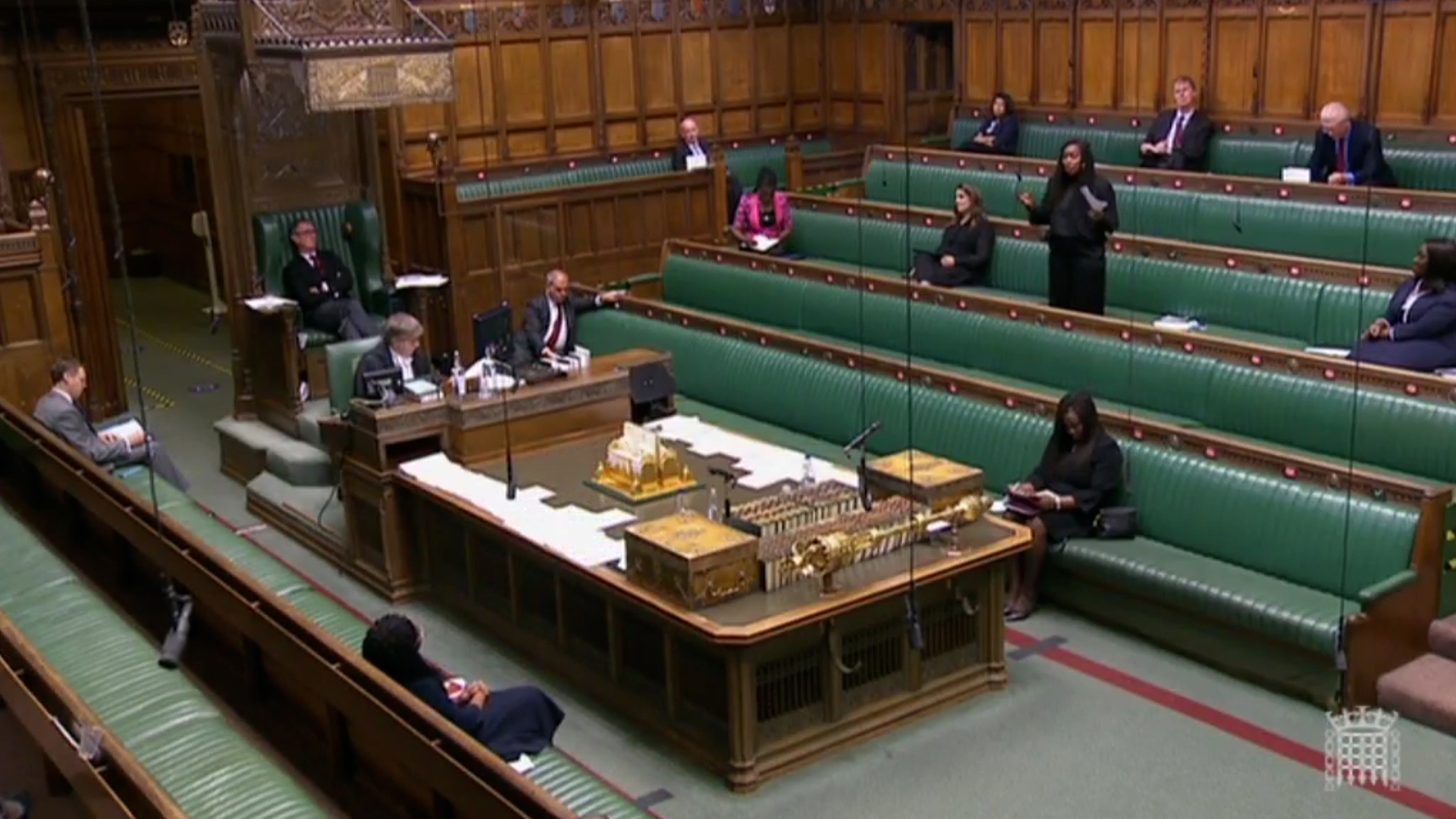 Wide view of Dawn Butler on her feet speaking in the House of Commons with MPs socially distanced during Black History month debate