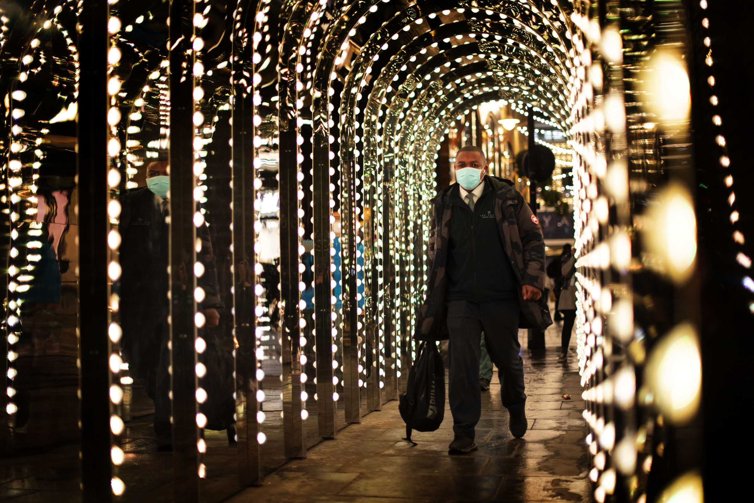 A man walks through an illuminated walkway in Covent Garden, London, which has moved into the highest tier of coronavirus restrictions as a result of soaring case rates.