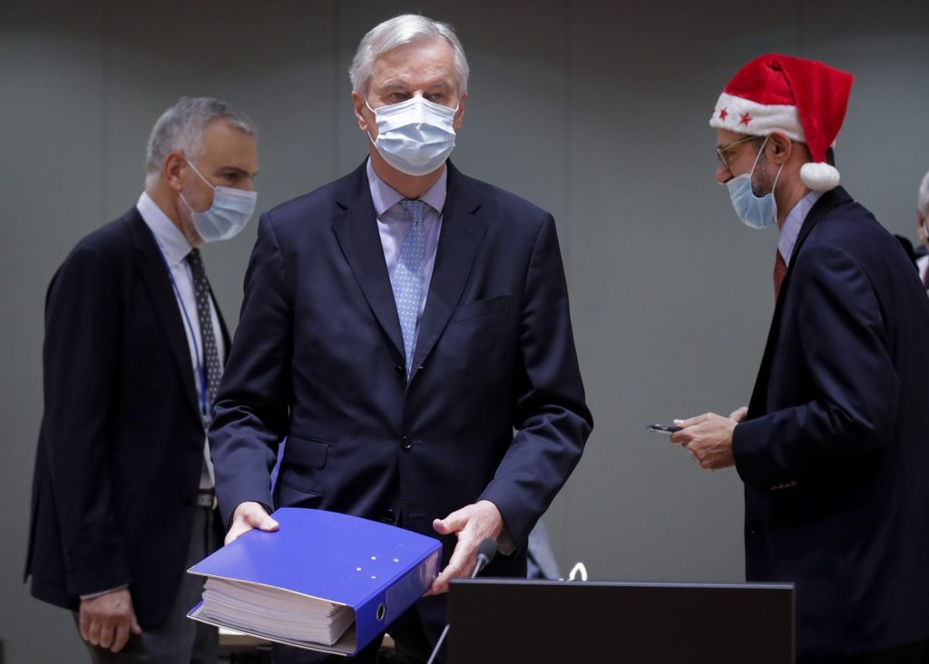 A colleague wears a Christmas hat as European Union chief negotiator Michel Barnier, center, carries a binder of the Brexit trade deal during a special meeting of Coreper, at the European Council building in Brussels, Friday, Dec. 25, 2020.