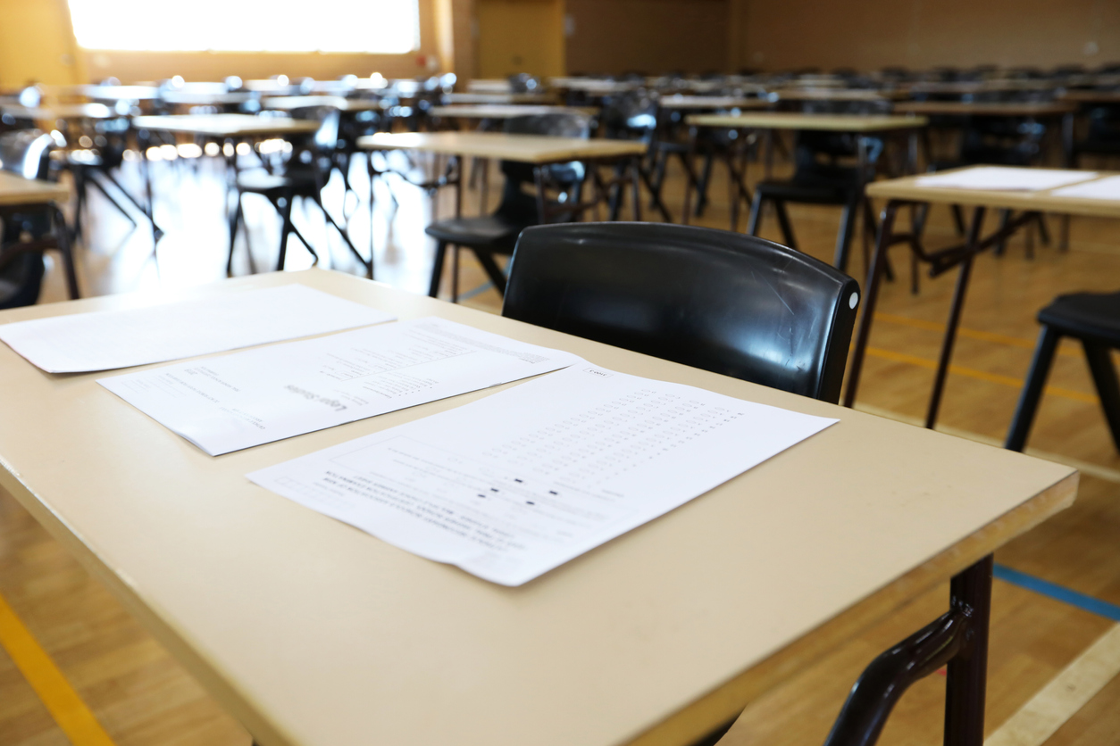 series of views of an examination hall or room images with exam tables set up ready for students. empty chairs and tables. End of school exams university entrance or higher school certificate scene.