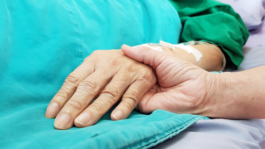 Oncologist doctor holding patient's hand in hospital. Showing all love, empathy, helping and encouragement. He has end stage cancer disease. Healthcare in end of life and palliative care concept