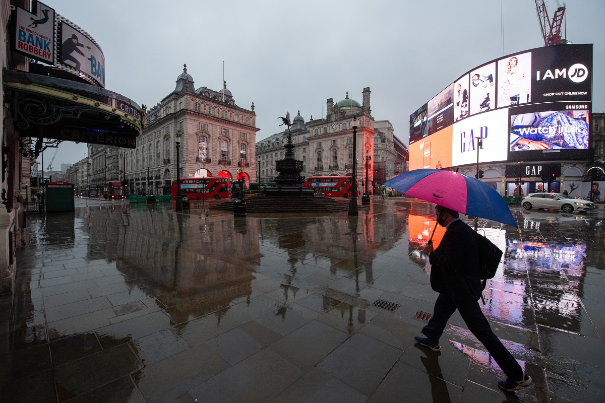 A man with an umbrella walks through a near empty Piccadilly Circus in London, during England's third national lockdown to curb the spread of coronavirus.