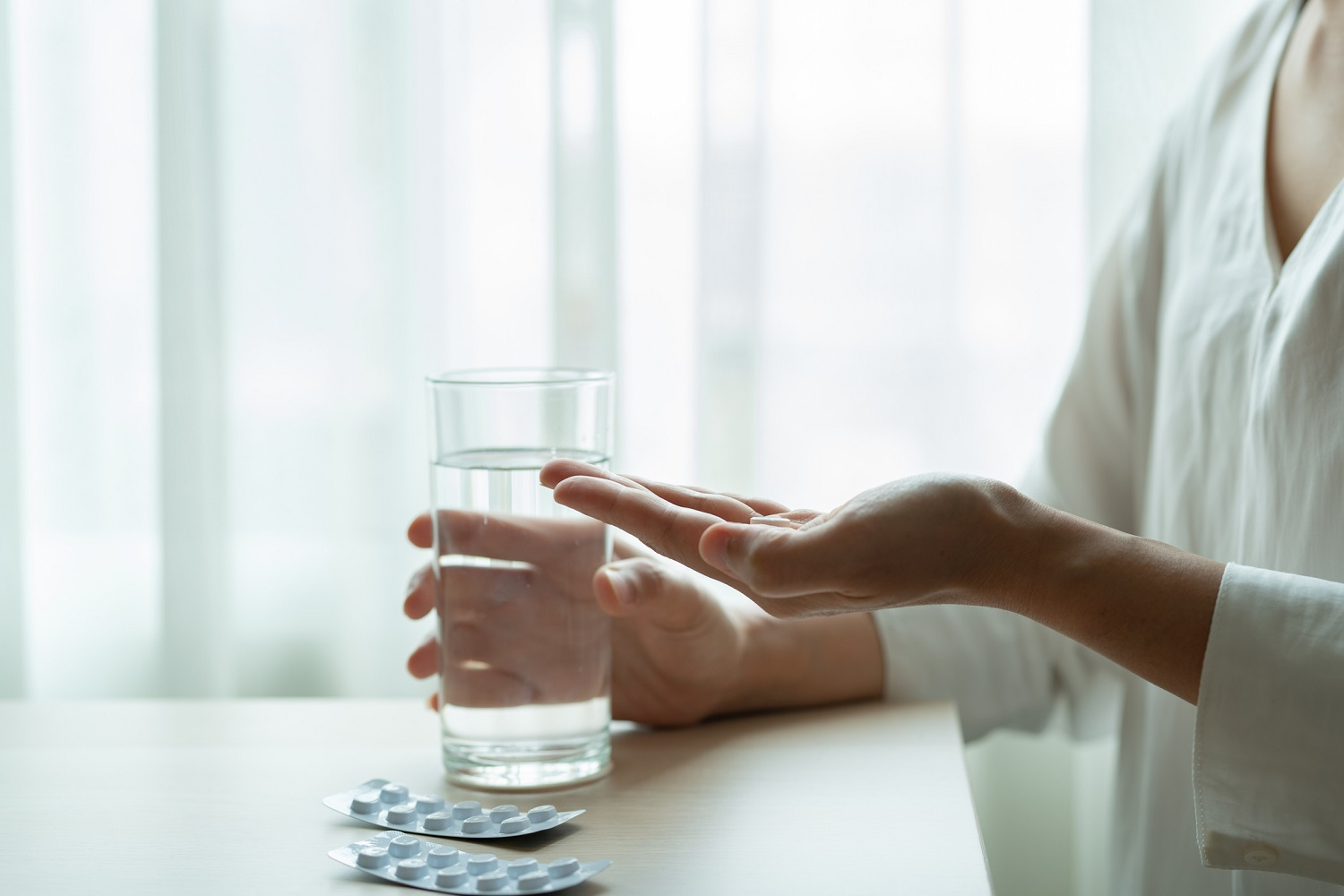 Woman holds medicine with a glass of water, healthcare and medicine recovery concept