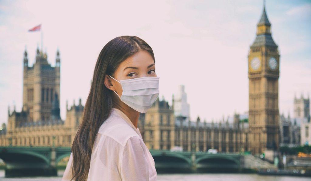 Corona virus travel corona virus spread prevention asian woman tourist wearing protective face mask on UK London city sightseeing holiday vacation. Famous british landmark background panoramic