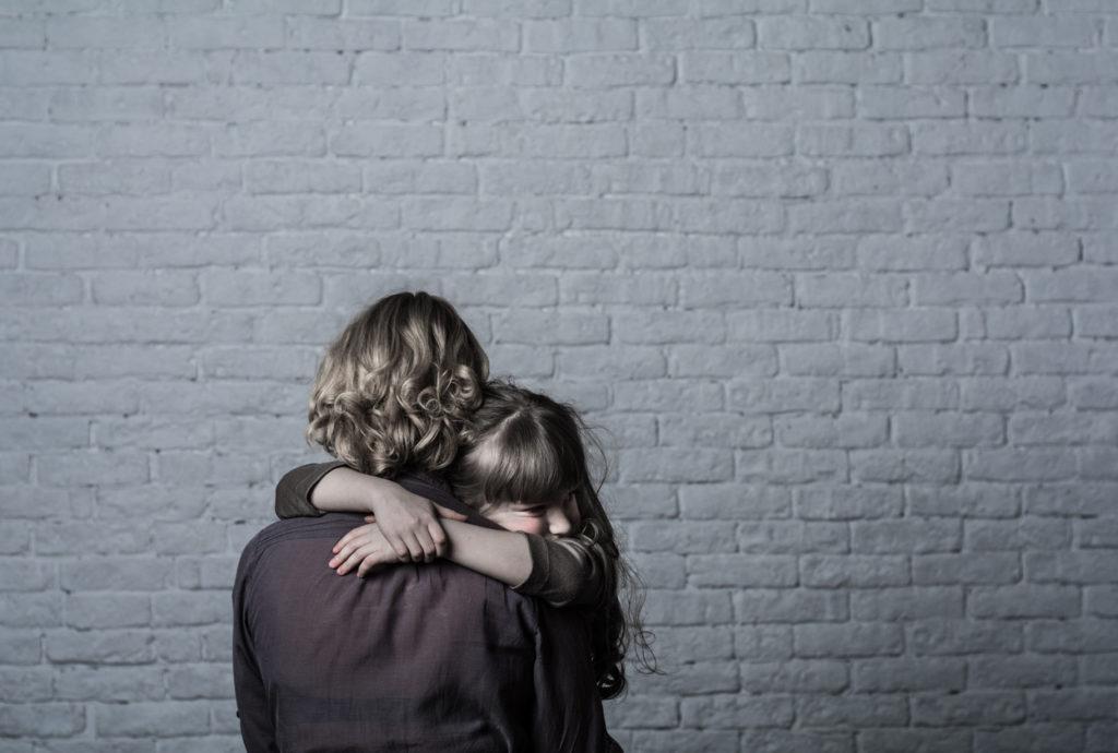 Girl hugging mother.