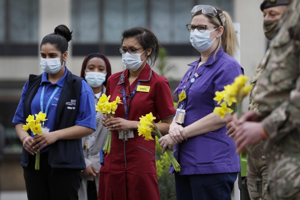 NHS staff lay flowers as they gather for a minute silence