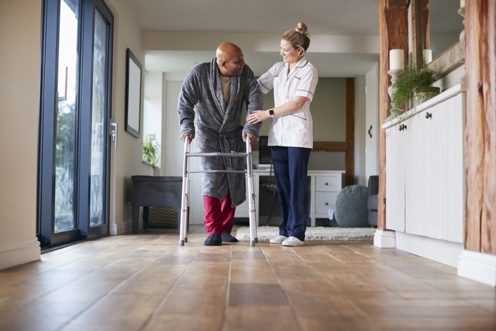 Senior Man In Dressing Gown Using Walking Frame Being Helped By Female Care Worker