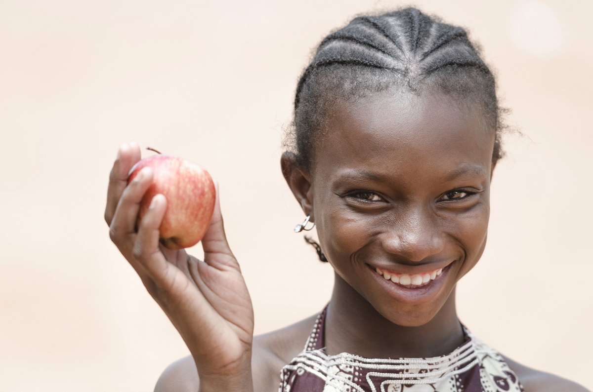 Vitality Healthy Eating Symbol: Smiling Young African Ethnicity Girl Apple