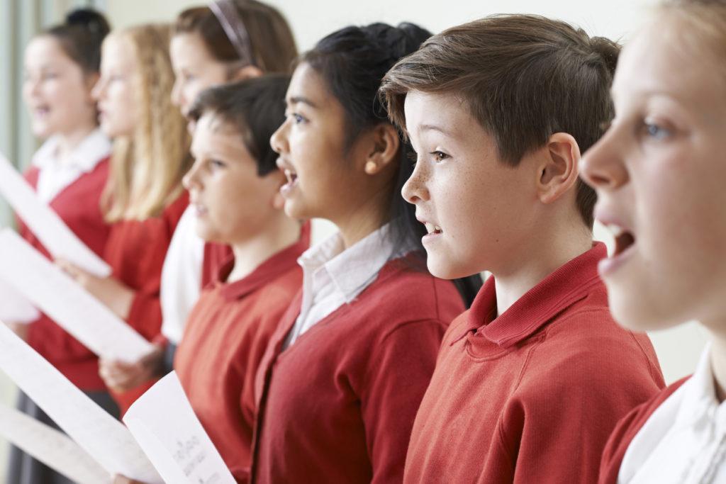 Group Of Children Singing In School Choir