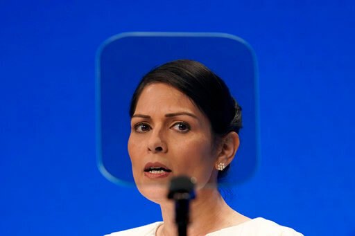Britain's Home Secretary Priti Patel looks at a teleprompter as she speaks at the Conservative Party Conference in Manchester, England, Tuesday, Oct. 5, 2021. (AP Photo/Jon Super)